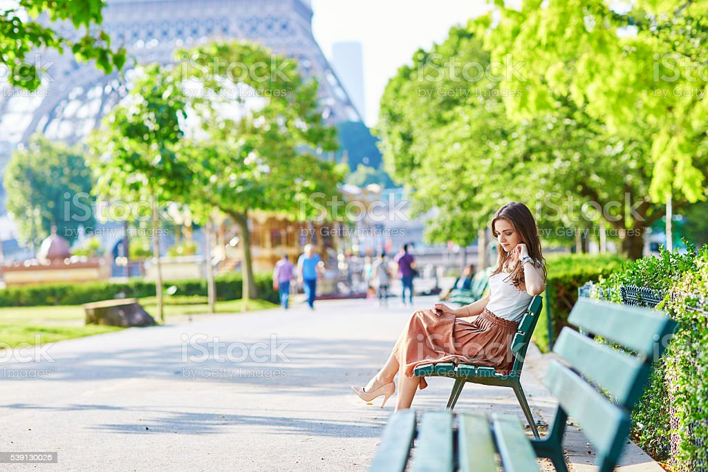Parisian woman sitting on the bench near the Eiffel tower stock photo