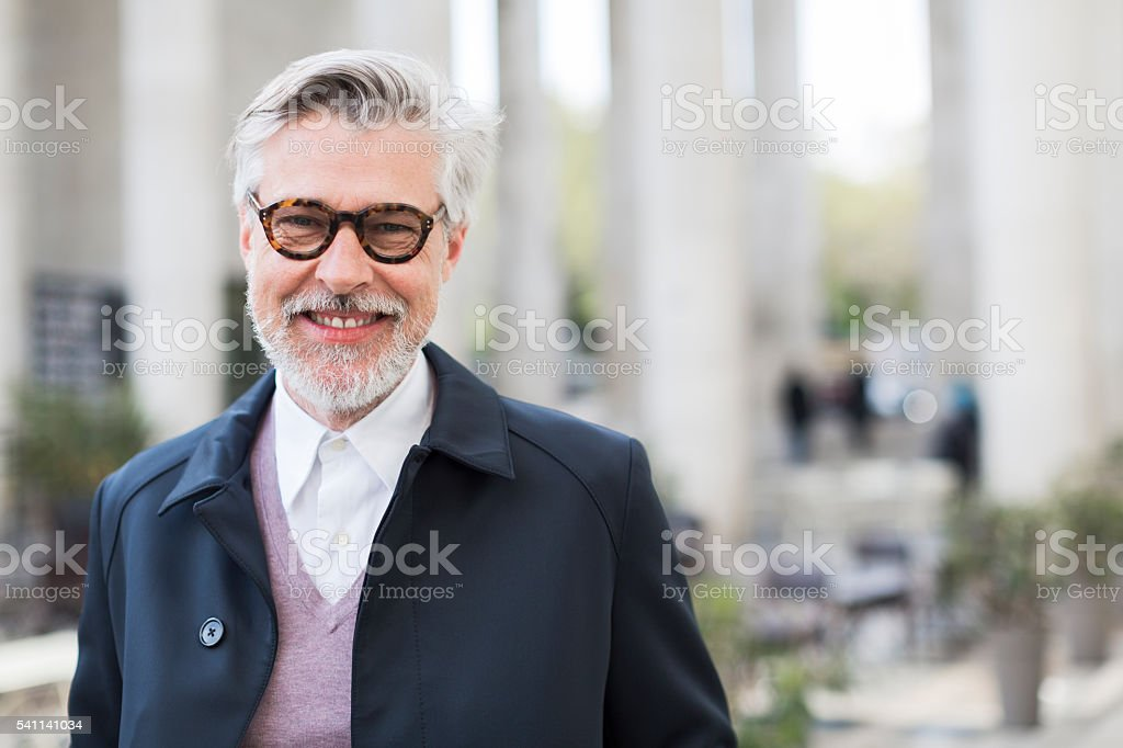 Parissien man smiling at camera on Paris streets stock photo
