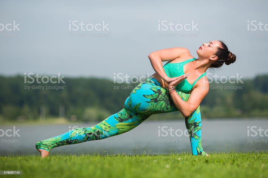 parivritta parsvakonasana. Yoga girl training outdoors on nature background. stock photo