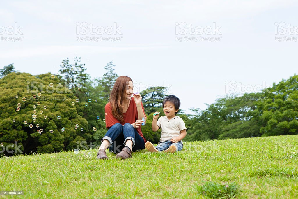 Park a happily family that is blowing a soap bubble stock photo