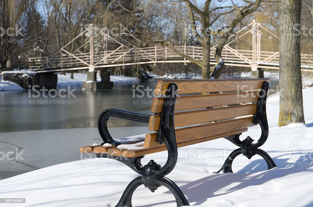 Park Bench by Bridge in Winter stock photo