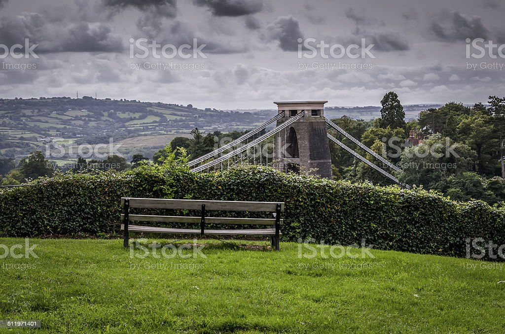 park bench over looking suspension bridge, bristol uk stock photo