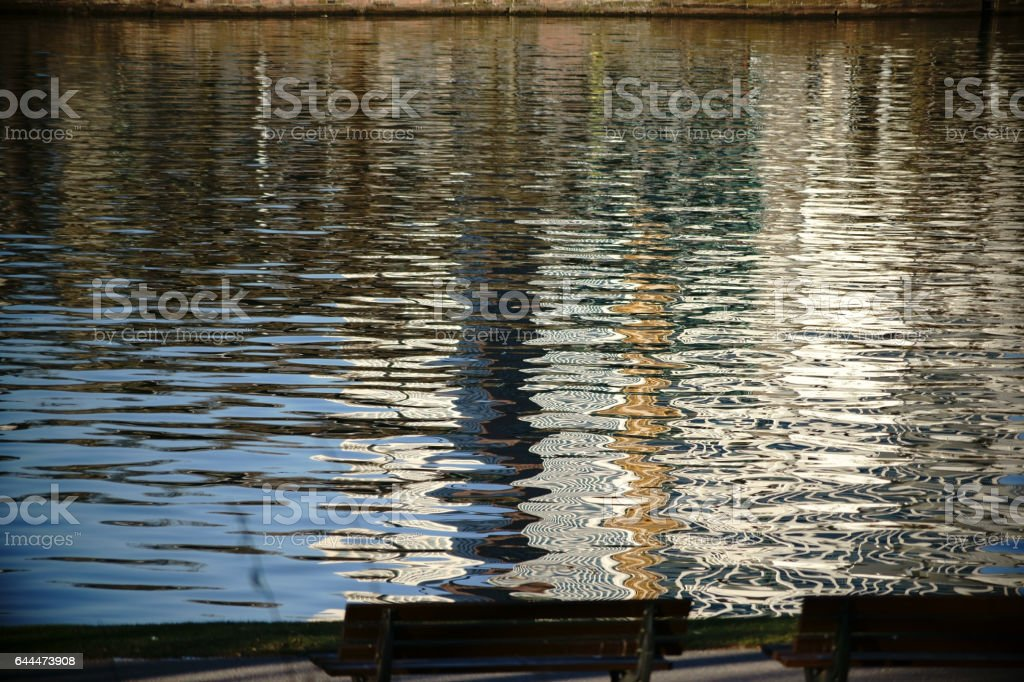 Park benches on the abstract water stock photo