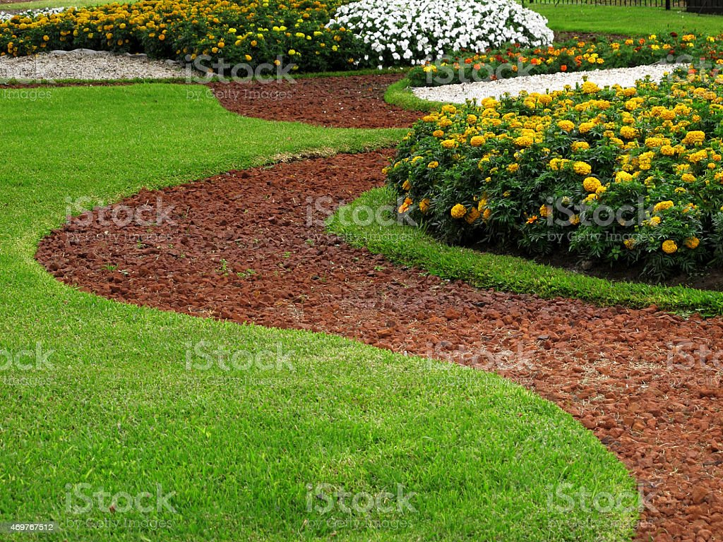 Park design stone pathways in grass with flower beds stock photo