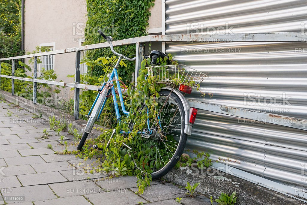 Parked and overgrown bicycle on the roadside stock photo