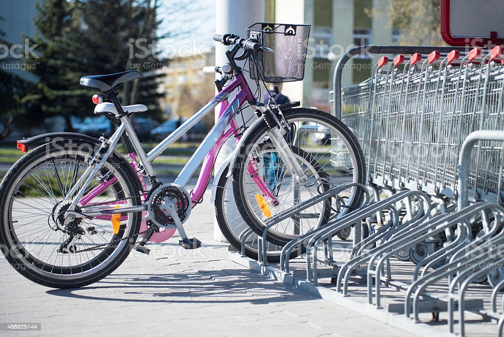 Parked bikes in a parcking rack in front of supermarket stock photo