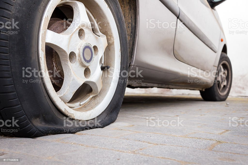 parked car with deflated tire stock photo
