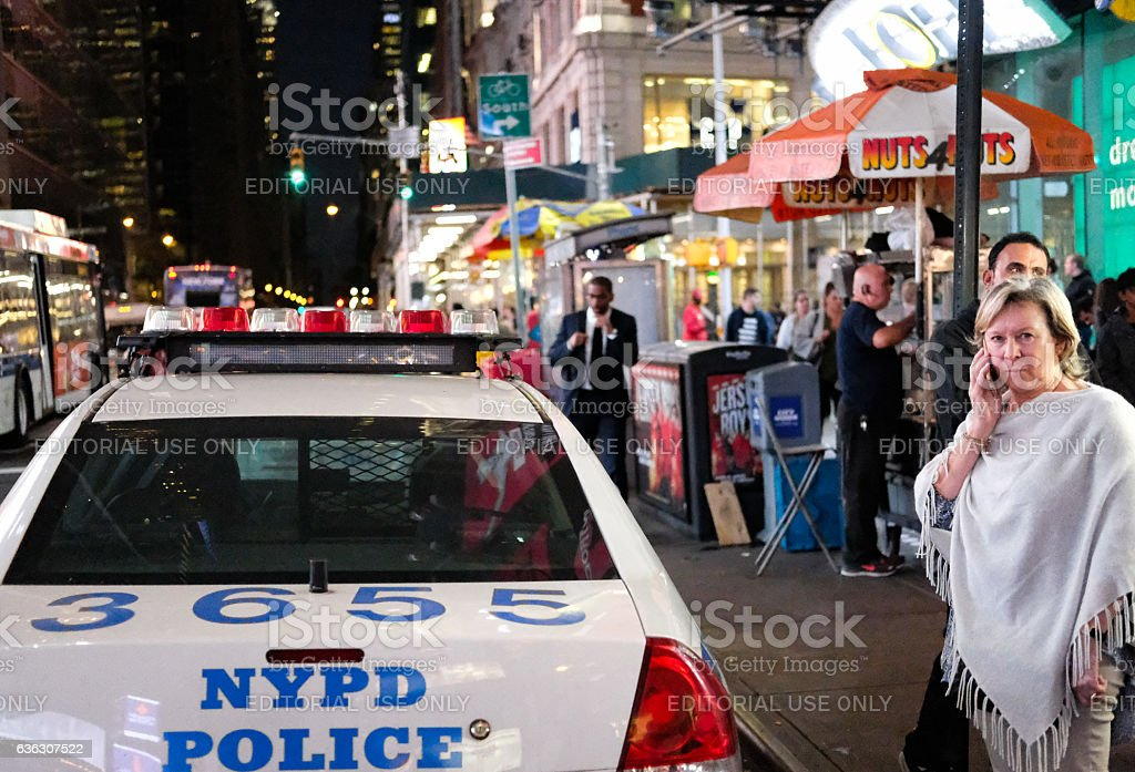 Parked NYPD vehicle next to a woman on a mobile phone stock photo