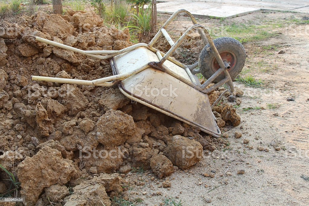 Parked wheelbarrow for construction at a building site. stock photo