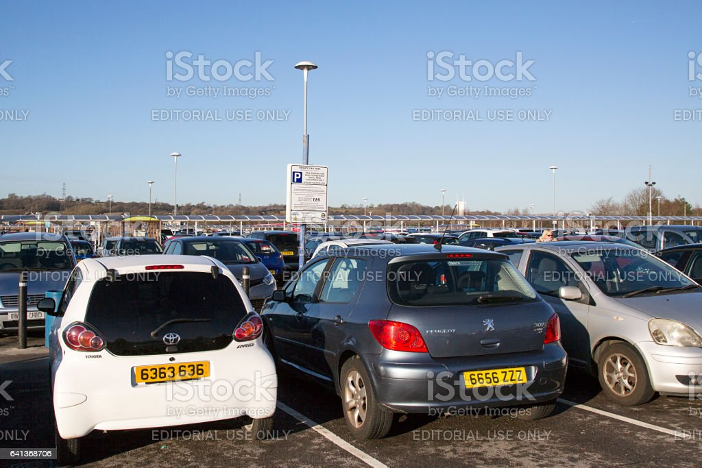 A parking notice stating the terms and conditions of use and fine if overstaying the four hour limit amongst the cars parked in the free car park at a Tesco Extra in Wales. stock photo