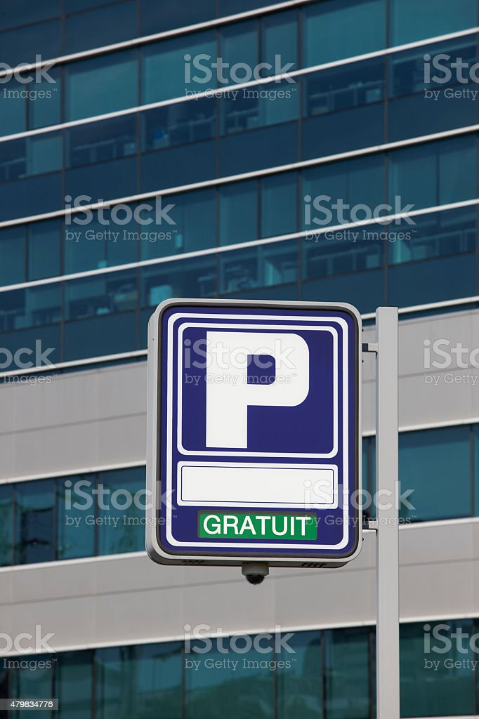 Parking signpost with gratuit text and modern building backgroun stock photo