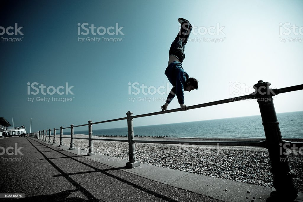 Parkour and freerunning rail handstand stock photo