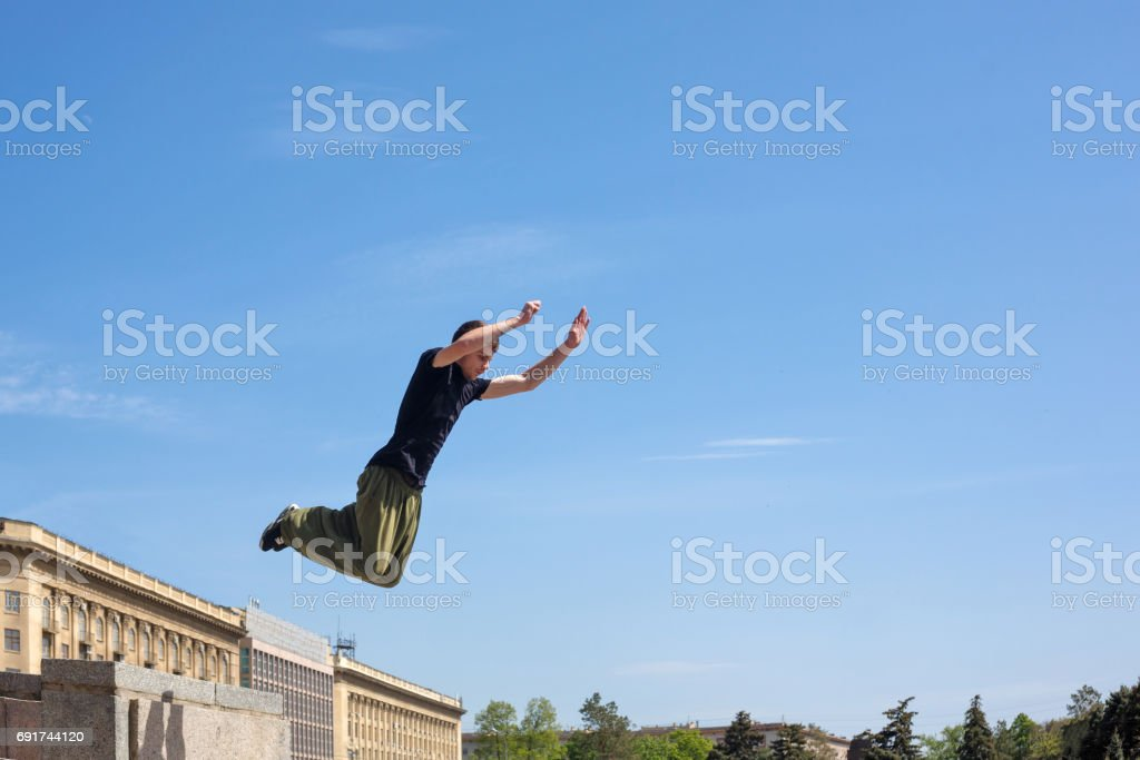 A young man is jumping from the wall. Parkour in the urban space....