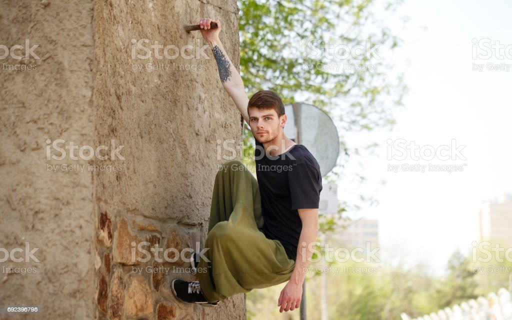 Young man hanging on the wall. Parkour in the urban space. Sports in...