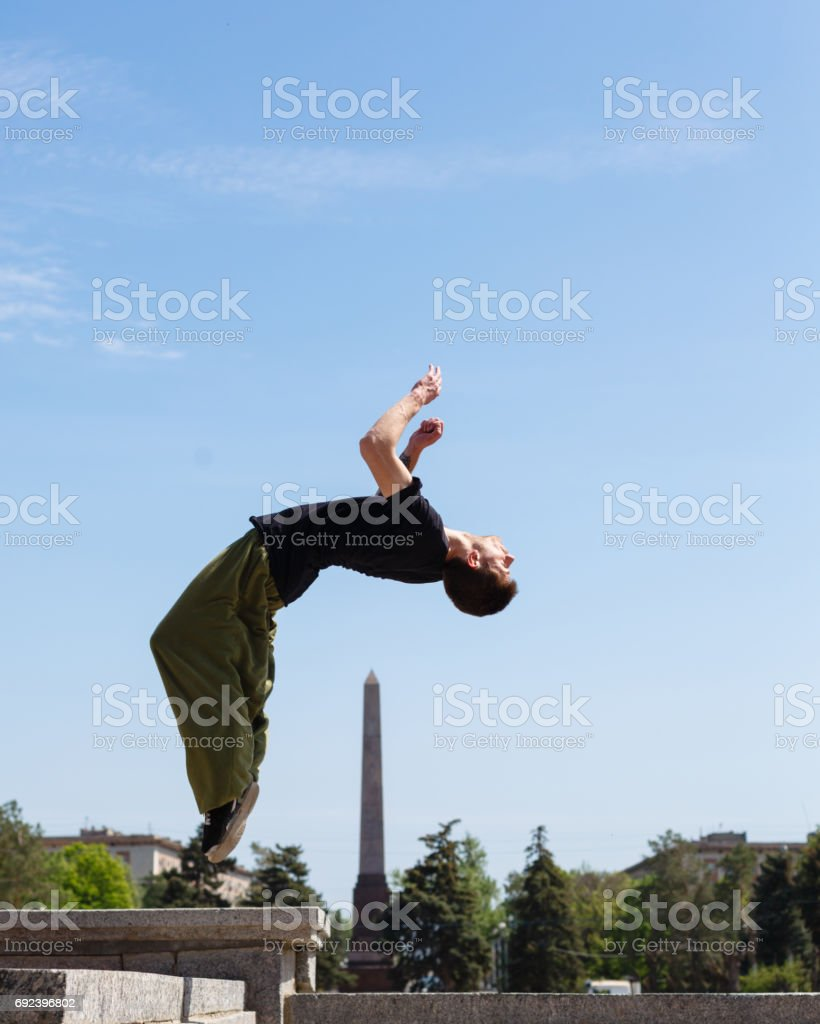 Young man doing a back flip in the background obelisk. Parkour in the...