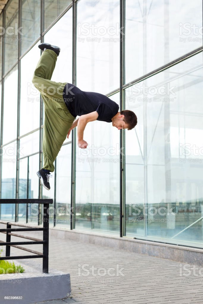 Young man jumps on a railing. Parkour in the urban space. Sports in...
