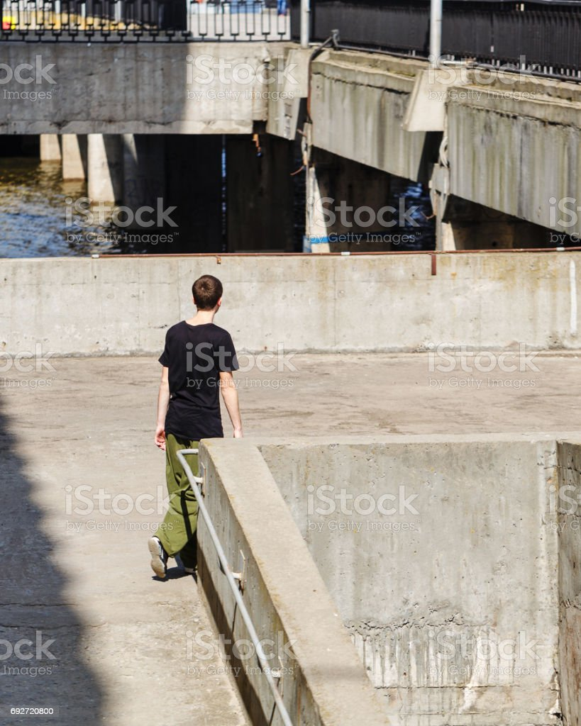 Young man walking on the pier. Parkour in the urban space. Sports in...