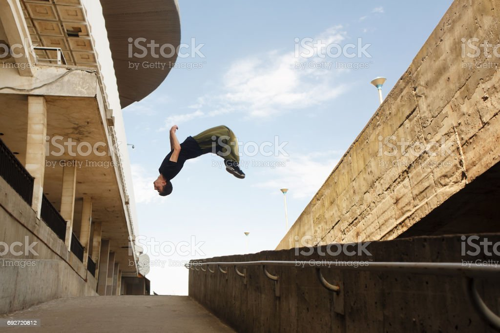 A young man does a back flip. Parkour in the urban space. Sports in...