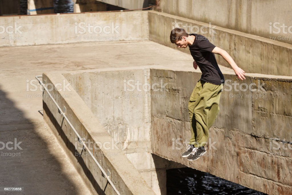 Young man jumping from a great height. Parkour in the urban space....