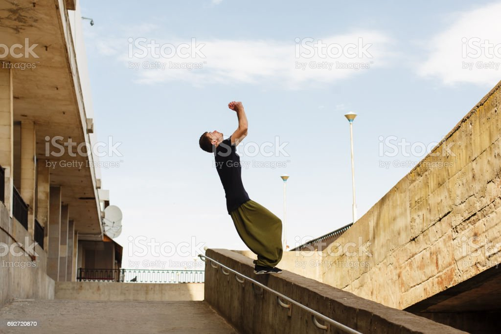 Young man back flip. Parkour in the urban space. Sport in the city....