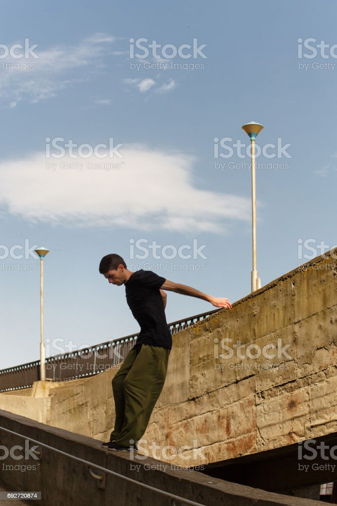 A young man is jumping from a high wall. Parkour in the urban space....
