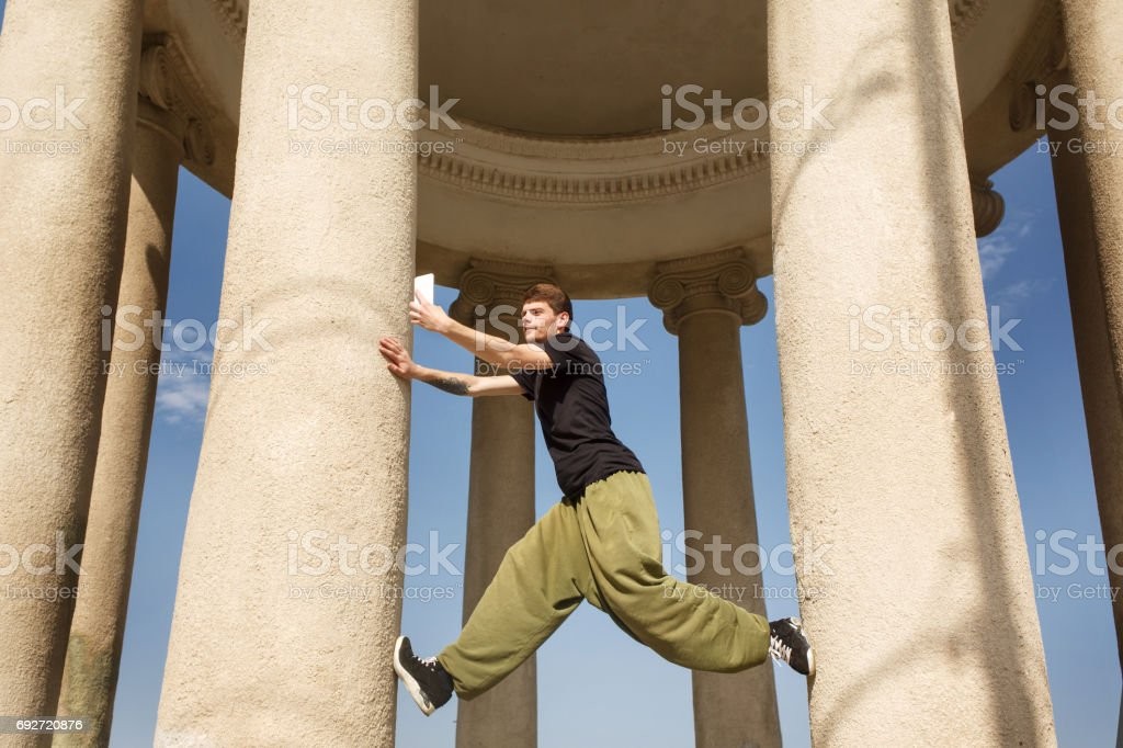 Young man climbs up honey columns. Parkour in the urban space. Sport...