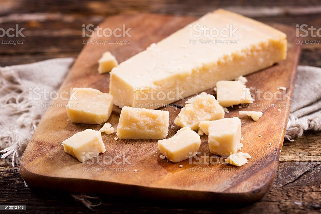 parmesan cheese on wooden board stock photo