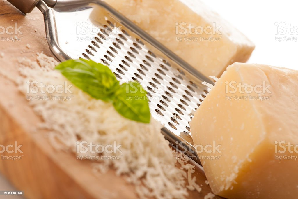 Parmesan cheese on wooden  plate isolated over white background stock photo