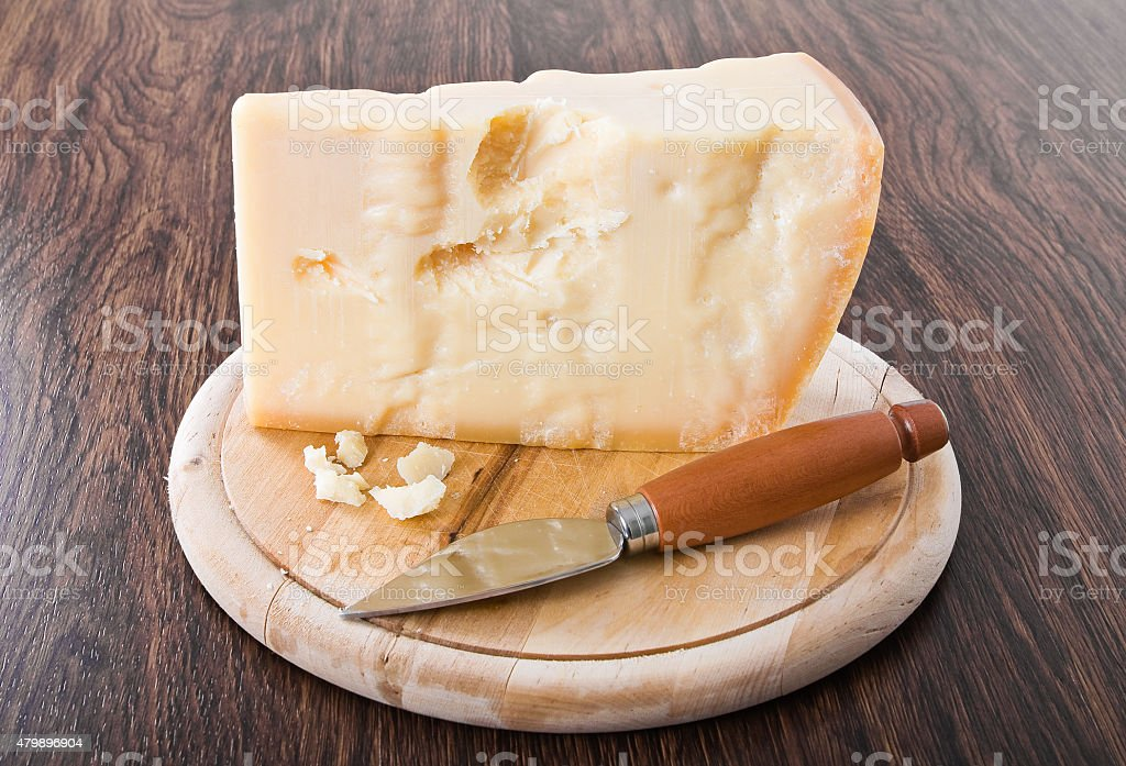 Parmesan cheese piece with knife. stock photo