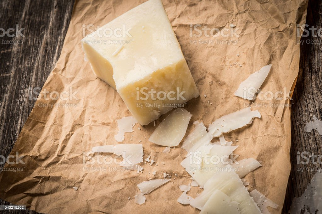 Parmesan cheese shavings on rustic background stock photo