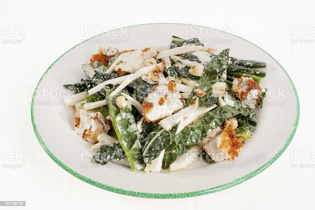 A parmesan chicken and kale salad on a white plate. royalty-free stock photo