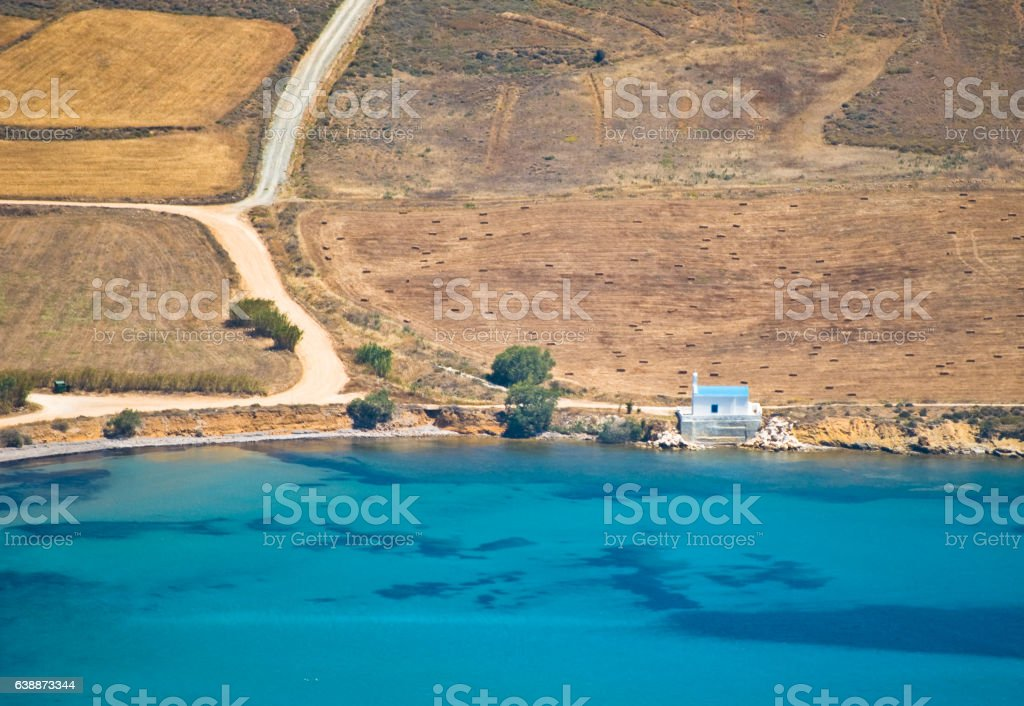 Paros landscape with Greek church between fields and the sea stock photo