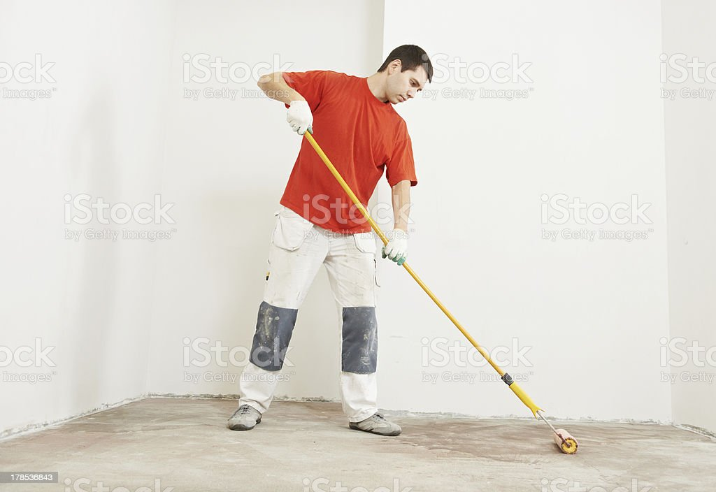 parquet layer with roller priming floor stock photo