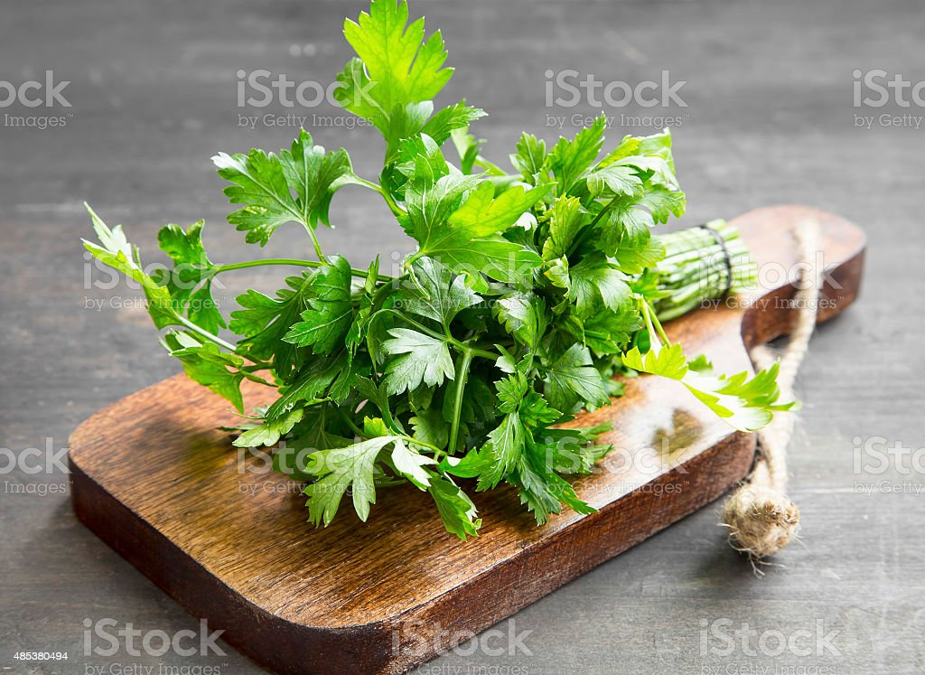 Parsley Culinary Herb on a Cutting Wooden Board stock photo