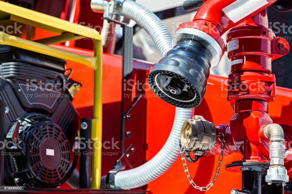 part of a fire truck in sunlight with hoses and valves stock photo