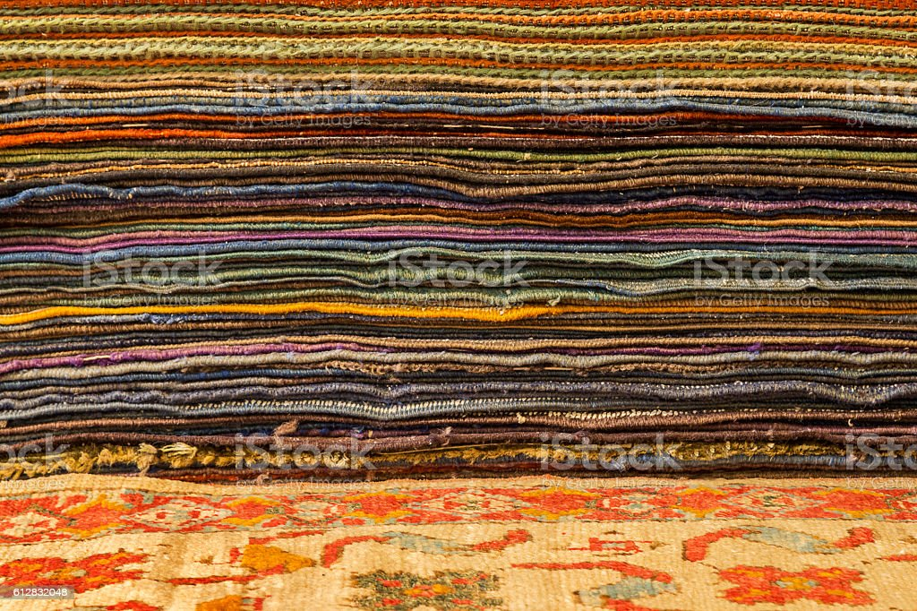 Part of an oriental carpet and pile of rugs stock photo