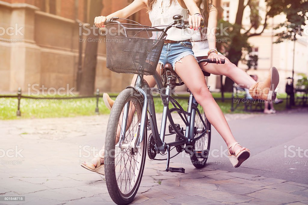 Part of boho girls during riding tandem bike stock photo