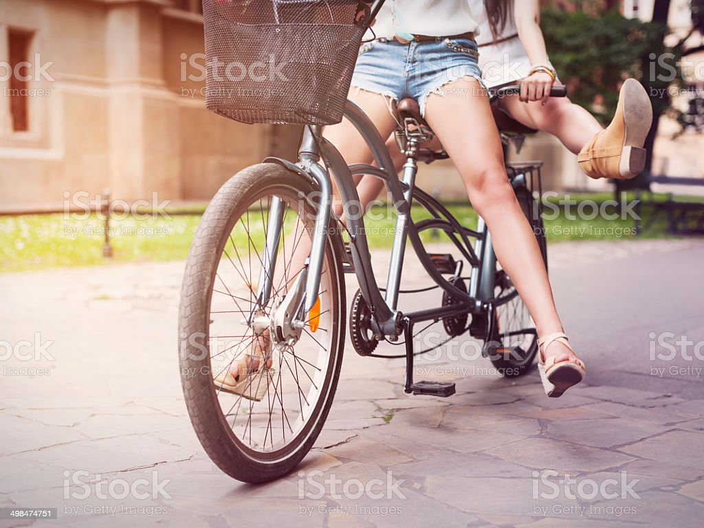 Part of boho girls legs during riding tandem bike stock photo