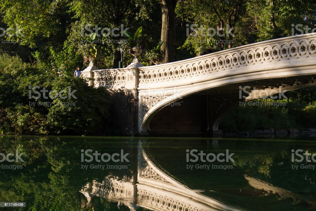 A part of Bow bridge clearly reflects on the lake at Central Park with sky stock photo