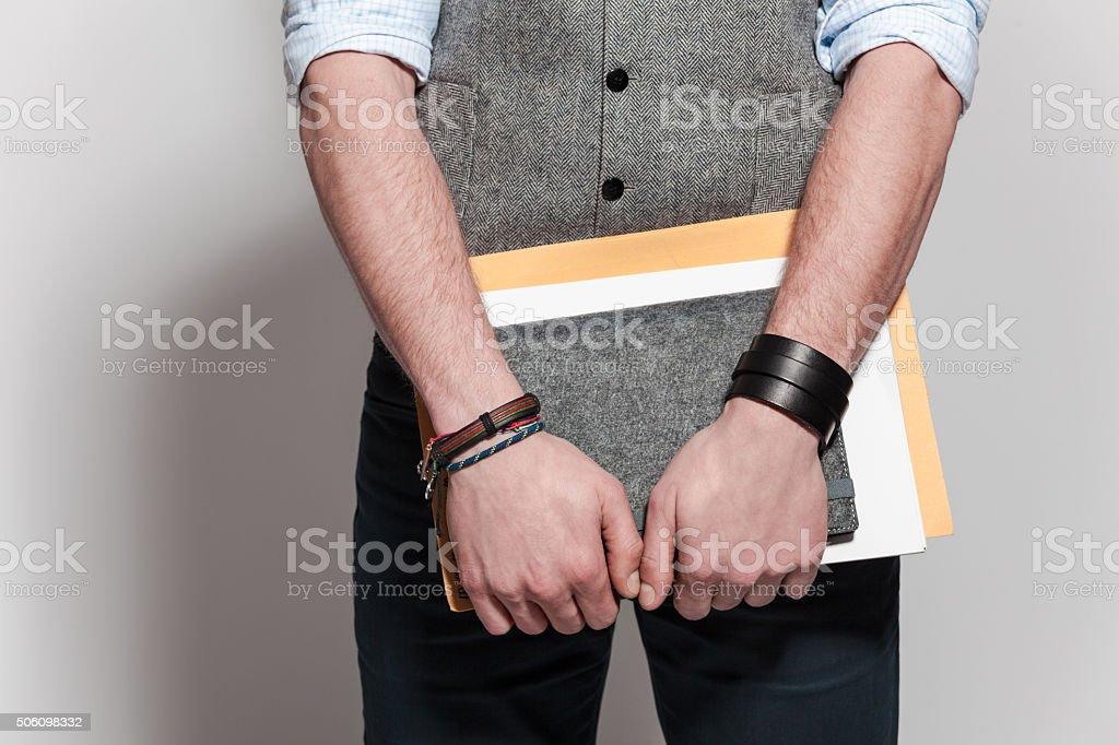 Part of fashionable man wearing tweed vest, holding notebooks stock photo