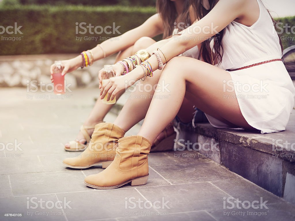 Part of hippie women sitting on curb stock photo