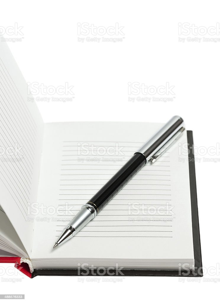 Part of opened notepad with pen. Isolated stock photo