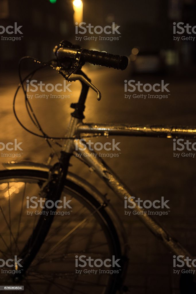 Part of the bicycle on the night rainy street in stock photo