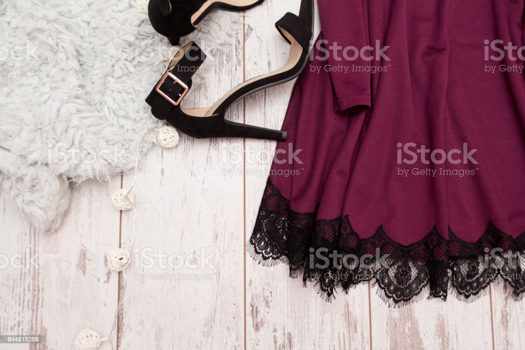 Part purple dress with lace and black shoes on a wooden background, fashionable concept, space for text stock photo