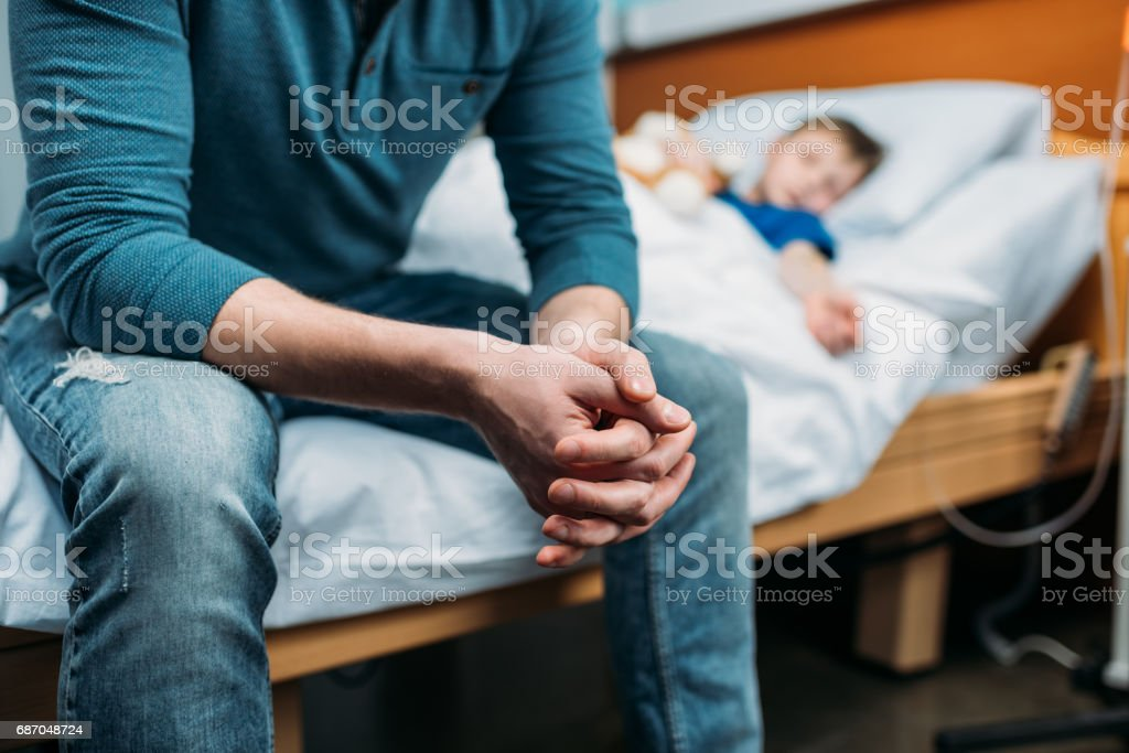 partial view of dad sitting near sick son in hospital bed stock photo