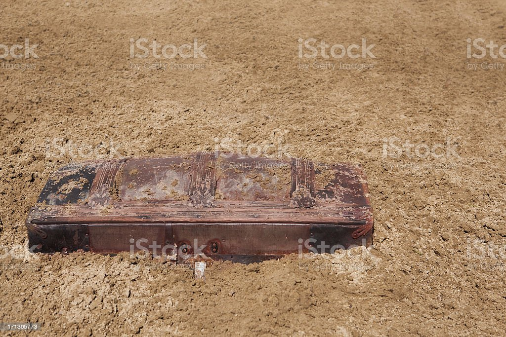 Partially burried treasure chest in the sand stock photo