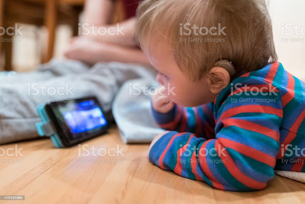 Partially deaf baby watching and listening lullaby on smartphone stock photo