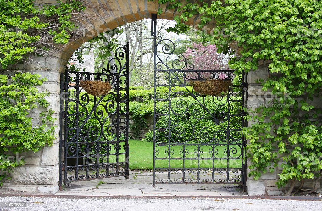 A partially open gate leading into a garden stock photo