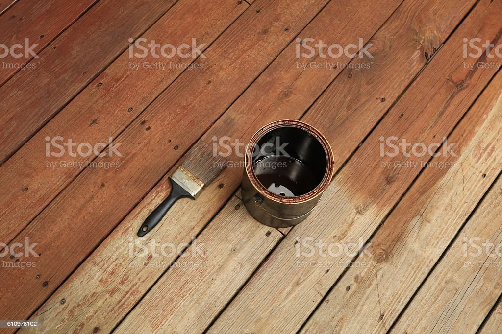 Partially stained deck; paint brush and a can of stain stock photo