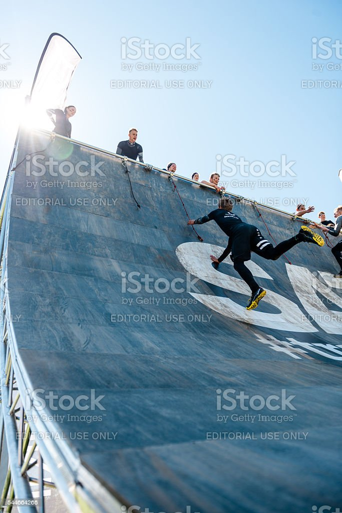 Participant in obstacle course race tries to overcome wall stock photo